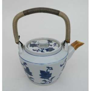 Bule de chá de porcelana azul e branco, com alça de bambu, revestida, decorado com flores azuis.Japão. alt 13 cm. diãmetro 17 cm.