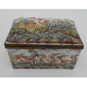 Caixa de porcelana Capodimonti, retangular, com cenas mitológicas,pintada à mão e acabamento de bronze.Apresenta danos. 19 x 11,5 x 12.