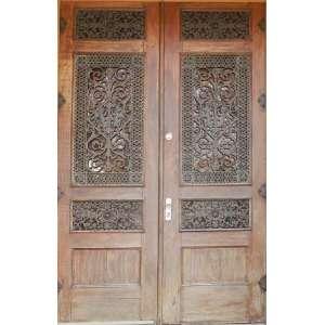 Porta de duas folhas, de carvalho, com importante trabalho em ferro forjado representando arabescos e anjos. Prancha de acrilico ambar no lugar dos vidros. 296 X 190cm. (duas folhas).