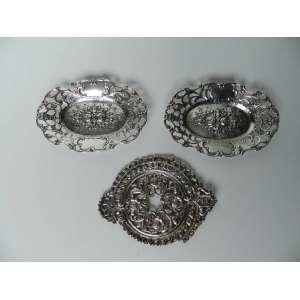 Lote com três peças, sendo duas bandejinhas de prata com galeria fenestrada e flores em relevo ao centro, altura 2cm, largura 14,5cm e 9cm de comprimento, e um aplique de prata representando flores,n.e.