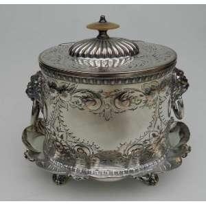 Caixa porta chá, executada em prata lavrada,com argolas laterais, sobre quatro pés tendo uma pega de marfim na tampa. altura 18cm, largura 15cm e 21cm de comprimento.