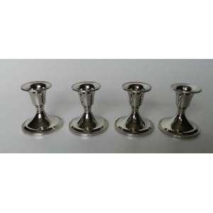 Lote com quatro castiçais de metal prateado,base ovalada, altura 6,5cm e 6cm de diâmetro.