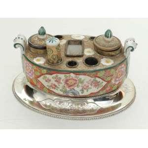 Tinteiro de porcelana, com desenho floral, base em prata de lei portuguesa, altura 9cm, largura 20cm e 13cm de comprimento.