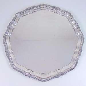 Grande salva de linhas sinuosas desenho semelhante a peças da prataria Inglesa executada em metal espessurado a prata. - 59 cm de diâm.