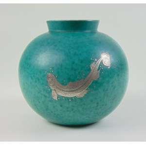 GUSTAVSBERG - ARGETA 1042 - Vaso de cerâmica esmaltada com delicado trabalho em prata ..Gustavsberg foi criada fora de Estocolmo, em 1786. A empresa teve sucesso na china Por volta do início do século XX, a empresa começou a produzir cerâmica com padrões florais, sob a direção de Wennerberg G.Wilhelm Kåge, um artista e potter que estudou com Henri Matisse, se juntou à companhia em 1917. Mais tarde, ele tornou-se diretor artístico e assumiu a empresa em uma nova direção. Ele é conhecido por seus produtos de grés e extraordinárias peças de porcelana, seus desenhos para utensílios de mesa e seus esmaltes Farsta e Farstarust - cobre e óxido de ferro, respectivamente - 15 cm de alt, 16 cm de diâm.