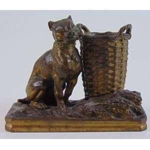 Escultura de bronze representando cachorro e cesto - 9 cm alt, 11 x 5 cm.