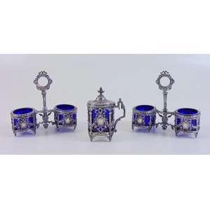 Elegante conjunto de saleiros, pimenteiros - 13 cm alt, 14 cm comp, 7 prof, mostardeira 10 cm alt, 5 cm diâm. em fina prata de lei trabalhada e interiores em cristal azul cobalto . Europa Sec XIX.