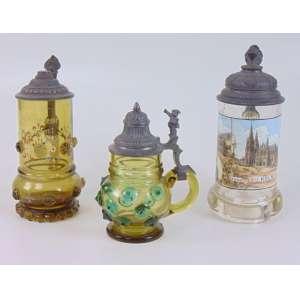 Conjunto de três tankards em vidro artístico e esmalte, tampas em estanho trabalhado Séc XIX- maior 22 cm alt. menor 16 cm alt. 1 peça no estado.