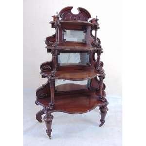 Elegante móvel expositor de madeira finamente lavrada guarnecido por espelhos e seus rodízios em latão. Inglaterra Sec XIX.- 150 cm alt, 105 compr, 44 cm prof.