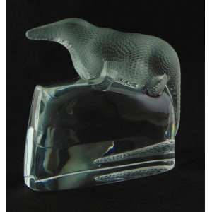 LALIQUE - Escultura em solido bloco de cristal representando crocodilo sobre rocha , assinado na base. França Sec XX. - 20 cm alt, 22 x 5 cm.