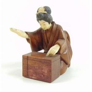 Netsuke de marfim e madeira representando Gueicha . Japão Sec XIX. - 5 cm alt, 4 cm compr.