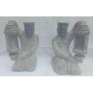 Par de esculturas executada em basalto representando serviçais a segurar lanternas . China Sec XX. - 68 cm alt, 40 x 34 cm.