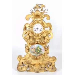 Belo relógio de mesa - Ferro dourado com placa de porcelana esmaltada com cena de paisagem - mostrador de porcelana Europa Sec XIX. - 60 cm alt, 35 cm compr, 10 cm prof.