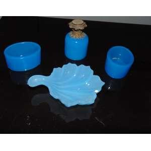 Lote com 4 peças , perfumeiro em opalina azul com detalhes em bronze com 8 cm de alt e 5 de diâm, concha em opalina azul com 13 x 9 cm e par de saleiro e pimenteiro medindo 4 cm de alt e 7 de diâm.