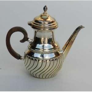 Bule de café de metal espessurada a prata, com gomos torcidos na base e alça de madeira. alt.22 cm.