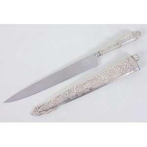 Punhal m metal finamente lavrado e decorado, no estojo original. 34 cm compr, bainha 26 cm compr. Brasil Sec XX