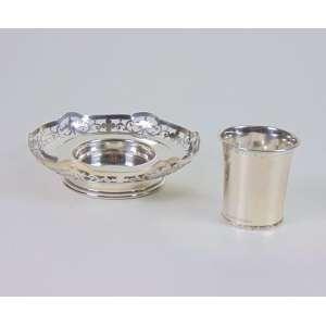 Lote composto por pequena cesta de prata de lei, contraste da cidade de Londres, recipiente e copo, teor 800, com a moeda ao fundo.