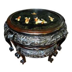 Mesa redonda com quatro bancos que se acoplam a ela, de madeira ebanizada ricamente entalhada com motivos chineses. Ao centro aplicação de pedras e madrepérolas em figuras sobre pintura de paisagem .