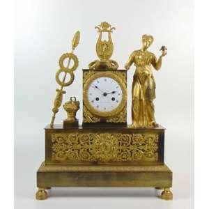 Badier á Laria - Relógio de mesa Império em bronze mostrador em porcelana asteroide lateral entortada - França Séc. XIX falta lhe o pêndulo - França Séc. XIX - 50 cm de alt, 37 de comp e 11 de prof.