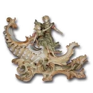 Nautilus de porcelana policromada e dourada, decorado com casal na parte superior e golfinhos estilizados na parte frontal, sem marcas de identificação de origem; 30 cm de altura. Apresenta pequenos quebrados no dedo da mão direita da moça e na lateral esquerda da concha. Europa, sec. XIX / XX.