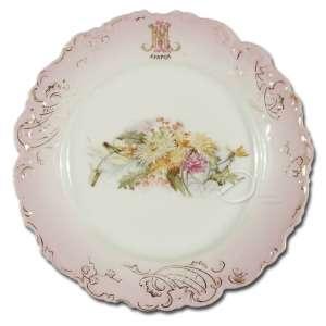 Prato de porcelana; aba rosa com relevos; borda recortada, com realces em dourado; apresentando monograma MNL - Ayapuá; no reverso marca de Vista Alegre; 23 cm de diâmetro. Portugal, séc. XIX