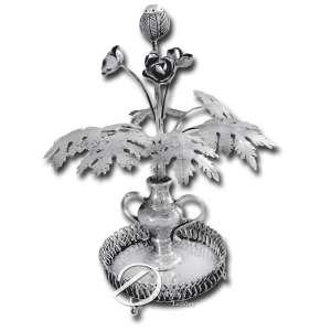 Paliteiro de prata repuxada e cinzelada, no formato de ânfora com 3 flores e uma papoula, base circular com varanda vazada apoiada sobre três pés, 21,5 cm de altura, sem marcas aparentes. Brasil, séc. XX.