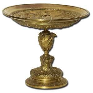 Centro de mesa de bronze ormolu; decoração no prato com cenas gregas em relevo; haste em seções, seguindo o mesmo padrão decorativo; base circular, decorada com flores e elementos repetitivos; 19 cm de altura e 20 cm de diâmetro do prato. Europa, sec. XX.