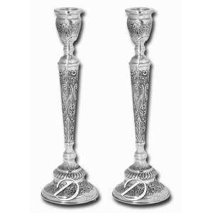 Par de castiçais de prata repuxada e cinzelada, haste decorada com volutas e elementos fitomórficos em relevo, base circular e marca de prata SP na base; 35 cm de altura. Brasil, séc. XX.