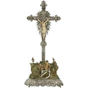Calvário - Conjunto escultórico representando Cristo crucificado de marfim; corpo em monobloco, braços encaixados, usando cendral drapeado, cravos das mãos encimados por ametista lapidada, perna direita sobre a esquerda fixadas por um só cravo, sem a coroa de espinhos. Cruz de madeira revestida por placa de prata decorada com ramos e flores bordeada por cordão, no alto placa com a legenda INRI, ponteiras de prata vazada decoradas com volutas em relevo, placa raiada de prata com seis rostos de anjos, sob os pés placa de prata com os Sagrados Corações de Jesus, Maria e José. Na base da cruz imagens de madeira esculpidas e policromadas representando Maria, sentada coberta com manto, e São João com túnica comprida e manto sobre os ombros, tendo a mão direita apontada para a cruz e a esquerda segurando o livro, abaixo num misto de pedras e ramagens quatro anjos ; ao lado da cruz dois anjos sem asas. Base retangular com cantos arredondados envolvidas por placa de prata com reservas decoradas em relevo por diversos símbolos cristãos; 43 x 29 x 100 de altura. Indo - Portugal, séc. XIX. - Apresenta falta dos dedos indicador e anelar da mão esquerda.