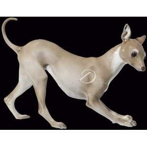 Escultura de porcelana esmaltada e vitrificada representando cachorro galgo italiano; na base de 25 x 10,5 cm marcas: Rosenthal, Selb-Plössberg, Germany, hundge-malt, 789; 20 cm de altura total. Alemanha, séc. XX. -