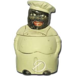 Porta condimentos, de porcelana policromada, representando cozinheiro com chapéu; tampa com frisos dourados e a inscrição: Cooky; no fundo externo, marca da manufatura Dearl / USA; 26,5 cm de altura. Estados Unidos, década de 1940.