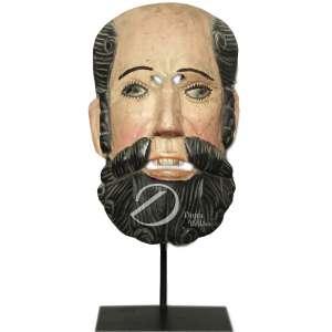 Conquistador Alvarado - Máscara de madeira lavrada e policromada representando rosto masculino com barba e cabelos penteados, olhos e boca vazados, sustentada por de metal; 37 cm de altura. América-espanhola, séc. XIX/XX.