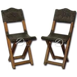 Par de cadeiras tesoura, de madeira, dobráveis com encosto e assento de couro lavrado; pernas retas e cruzadas fixadas por travas; 86 cm de altura. Brasil, sec. XIX.