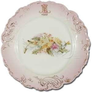 Prato de porcelana; aba rosa com relevos; borda recortada com realces dourados; apresentando monograma MNL - Ayapuá; no reverso marca de Vista Alegre; 23 cm de diâmetro. Portugal, séc. XIX.