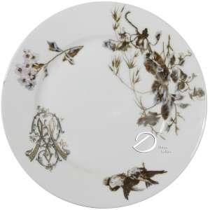 Prato de porcelana monogramada, aba com borda lisa, decorada por ramos e pássaros e deslocada à direita EW entrelaçado, sem marcas aparentes; 22 cm de diâmetro. França, séc. XIX.