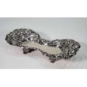 Belíssimo berço para espevitadeira em prata de lei - L coroado e marca do prateiro V.A.D. - plano liso assentado sobre quatro pés - 24 x 11,5 cm - Portugal, séc. XIX