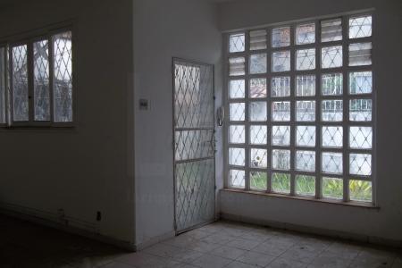 Casa antiga com 2 salas com piso em cerâmica, 2 quartos, banho em cerâmica, área de serviço coberta e DCE.