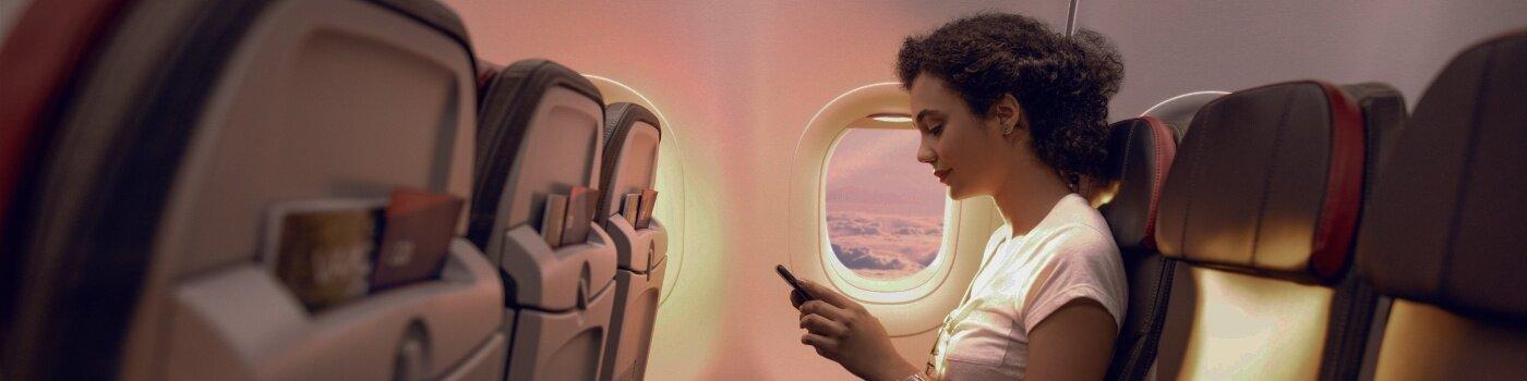 Mujer revisa celular en cabina de avión