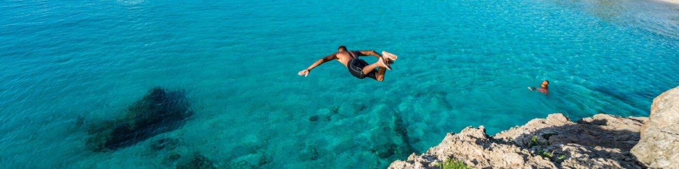 homem pulando no mar