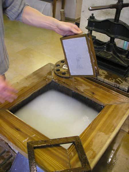 Polpa de celulose sendo colocada na máquina de papel.