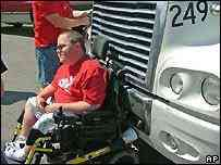 Caminhão empurra sujeito em uma cadeira de rodas pelas estradas
