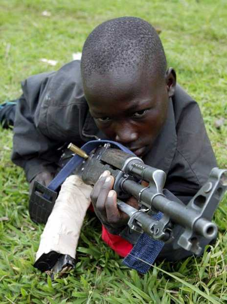 A child soldier practices with a machine gun in an ethnic Hema militia camp near Bunia in the Democratic Republic of Congo, June 15, 2003. Calm returned to Bunia allowing residents to venture out of their homes on Sunday, a day after French troops clashed with local tribal militia for the first time. French troops have begun deploying in the town over the past few days as part of an international force to protect civilians from fighting between rival ethnic Hema and Lendu militia.     REUTERS/Jacky Naegelen