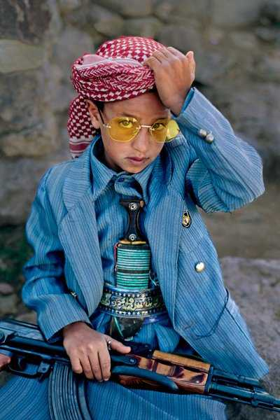 Dressed-up boy with gun in Hajjah, Yemen, 1999. A boy in Hajjah becomes a little man to attend a wedding., donning gear worn by many highland males - a head covering, a dagger, and a Kalashnikov rifle.Yemen UnitedNational Geographic, April 2000 final print_milan Dressed-up boy with gun in Hajjah, Yemen, 1999. A boy in Hajjah becomes a little man to attend a wedding., donning gear worn by many highland males - a head covering, a dagger, and a Kalashnikov rifle.