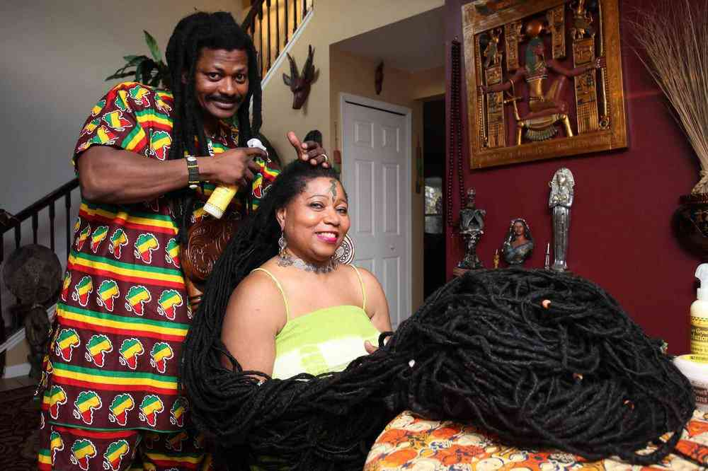 *** EXCLUSIVE - VIDEO AVAILABLE *** ORLANDO, FL - MARCH 1: Asha Mandela gets her hair tended to by her husband Emmanuel Chege at home on March 1, 2016 in Orlando, Florida. The woman with the world?s longest hair has found love with a hair stylist whose massive dreadlocks rival her own. Real life ?Rasta-Rapunzel,? Asha Mandela, has dreadlocks that measure 55ft - longer than a London bus. Now the 50-year-old, from Florida, has married her dream man, Emmanuel Chege, a qualified hair stylist from Kenya. PHOTOGRAPH BY Ruaridh Connellan / Barcroft USA UK Office, London. T +44 845 370 2233 W www.barcroftmedia.com USA Office, New York City. T +1 212 796 2458 W www.barcroftusa.com Indian Office, Delhi. T +91 11 4053 2429 W www.barcroftindia.com