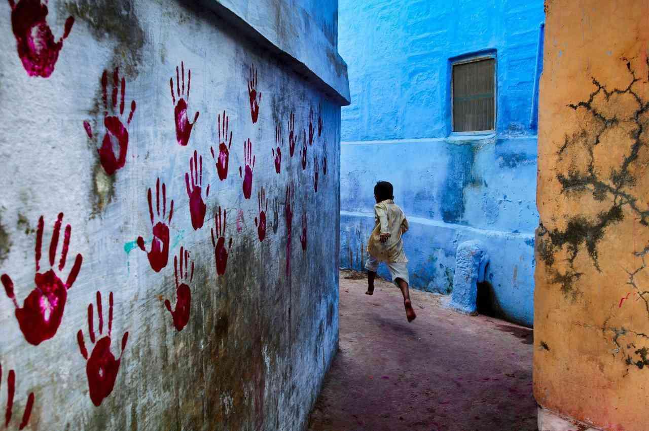 Menino no meio do vôo, Jodhpur, Índia, 2007 Ao pé do vasto Forte de Mehrangarh, pode-se encontrar a Cidade Azul, um pequeno labirinto bem forte de casas localizadas no norte de Jodhpur. Em uma das ruas estreitas, um menino foge da câmera de McCurry. Balancin