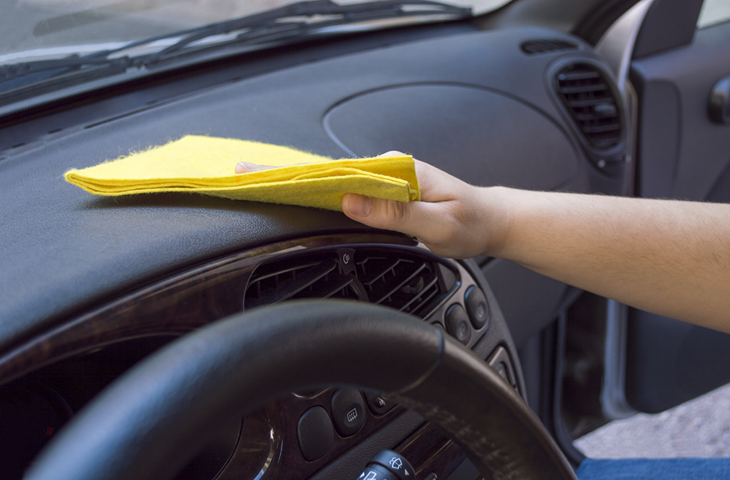woman cleaning the car interior with yellow cloth