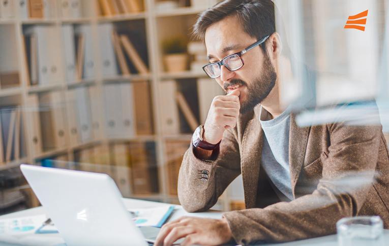 Um homem de óculos sentado de frente para um notebook em um escritório