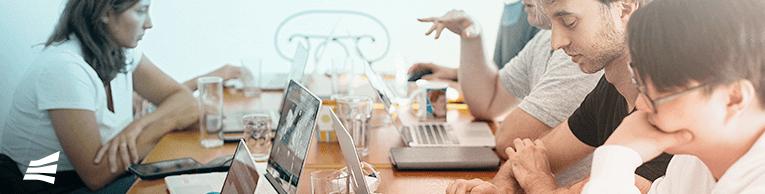 Pessoas trabalhando numa mesa com computadores