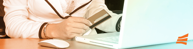 Mulher segurando cartão de crédito e mexendo no computador