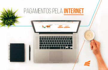 Pagamento pela internet: notebook, caderno, caneta, café e uma planta